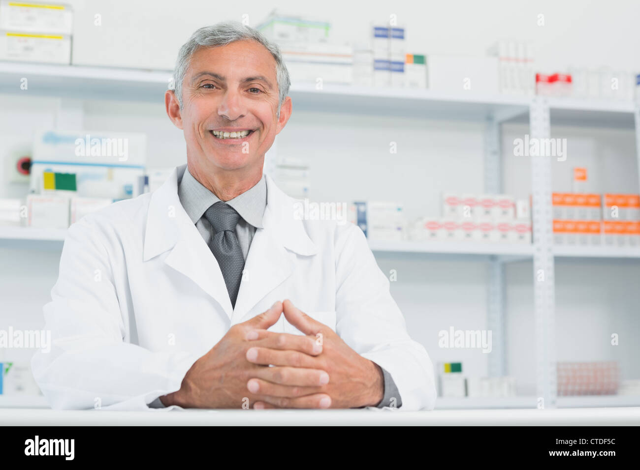 Happy male pharmacist with his hands joined on a counter - Stock Image