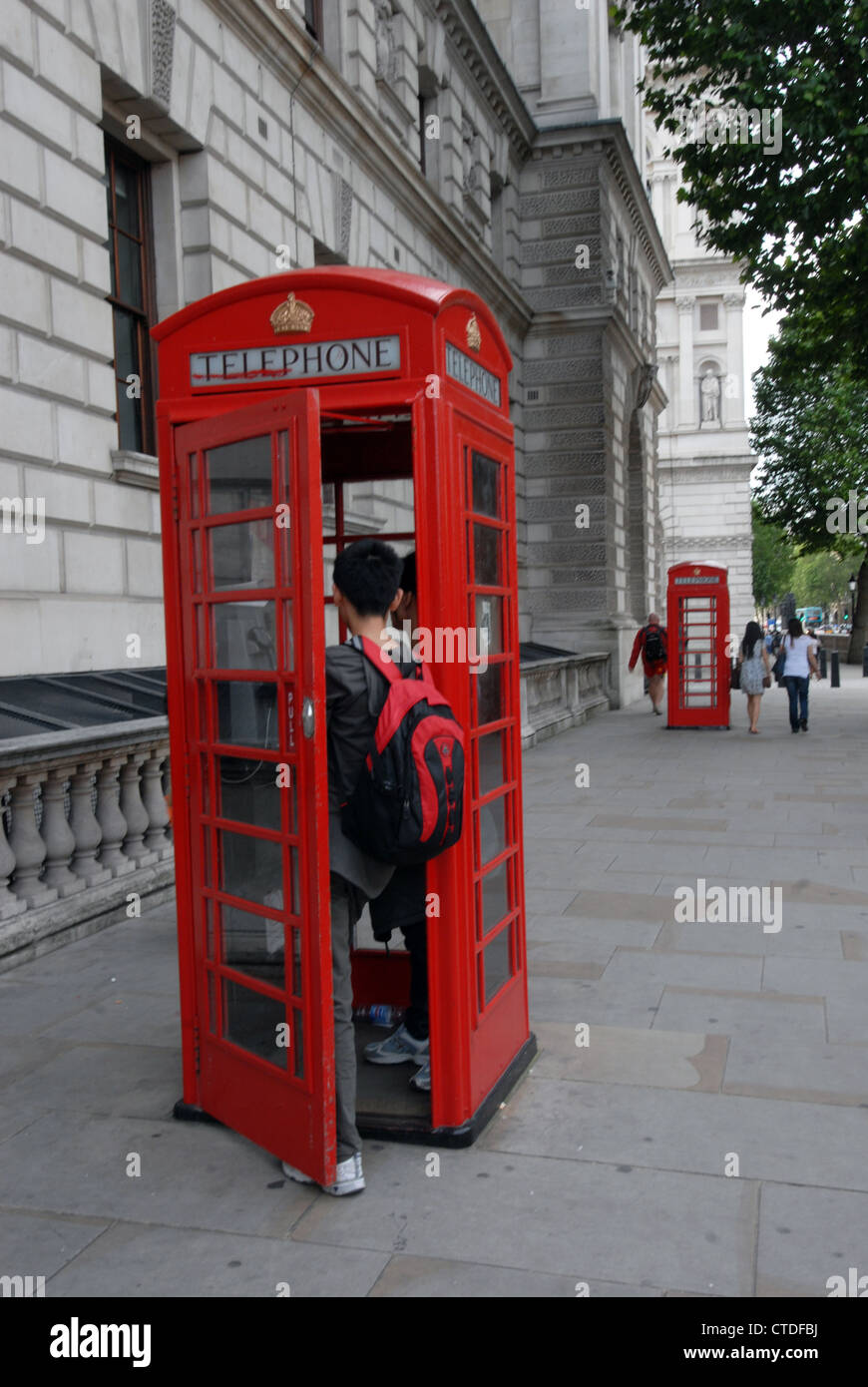 Telephone kiosks in use  on Whitehall pavement in  London England - Stock Image