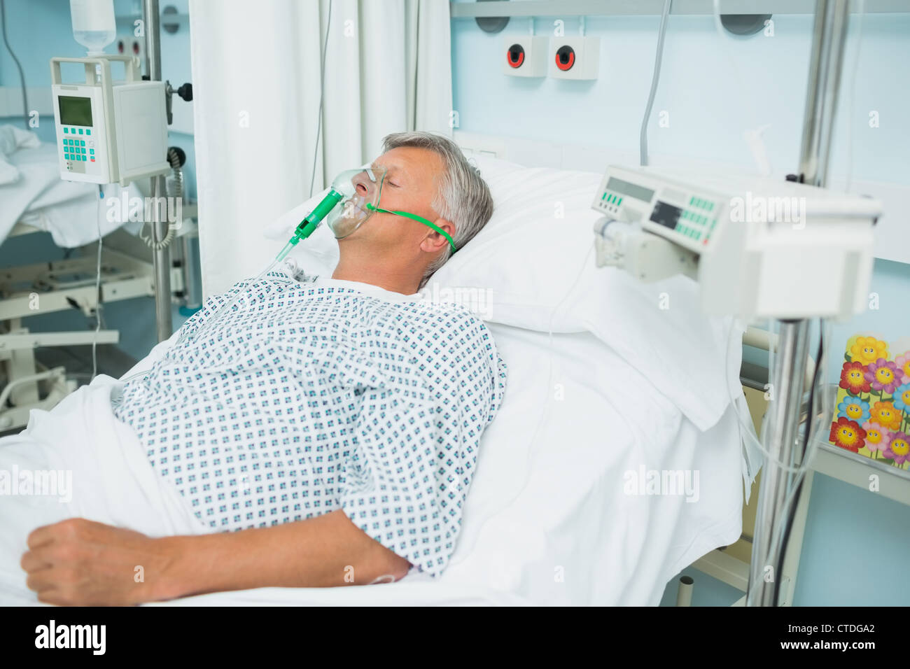 Unconscious patient lying on a bed with an oxygen mask on