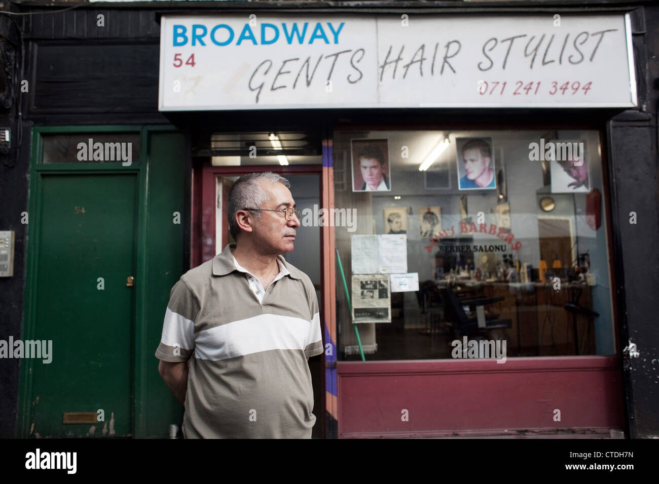 Hair dresser Ismael in front of his barbers salon in Broadway Market. - Stock Image