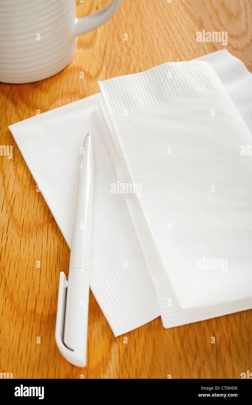 White napkin or serviette and pen on oak surface, ideal for notes and phone numbers, and that great idea you had - Stock Image