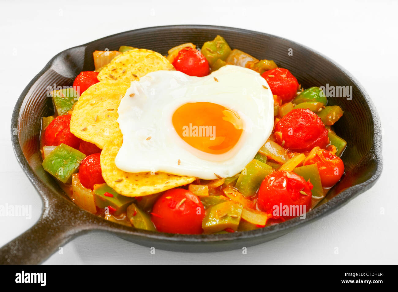 A cast iron skillet containing huevos rancheros, salsa rancheros topped with corn chips and a fried egg. - Stock Image