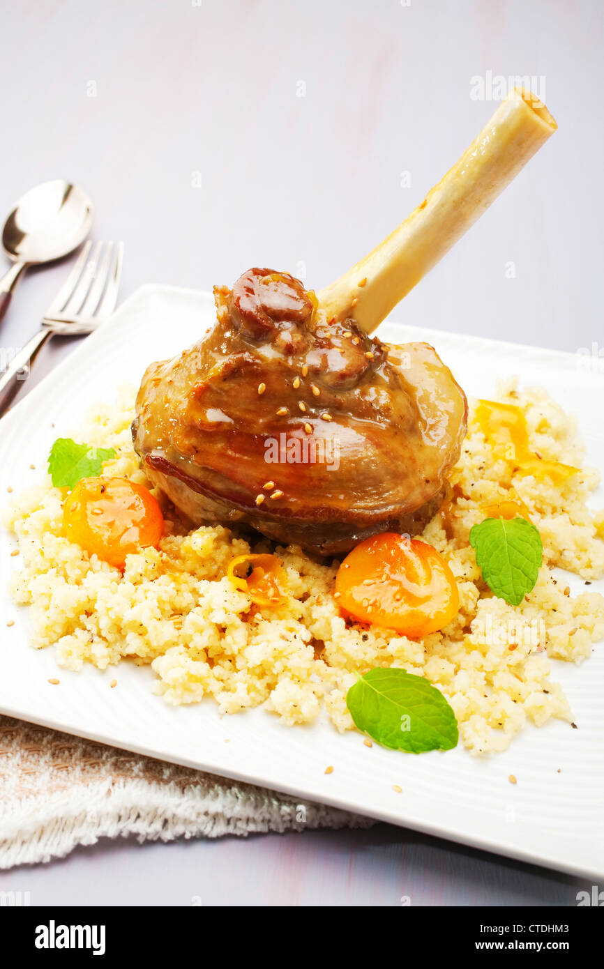 Moroccan tagine, lamb shank cooked with ginger, cinnamon, honey and apricots, served over couscous. - Stock Image