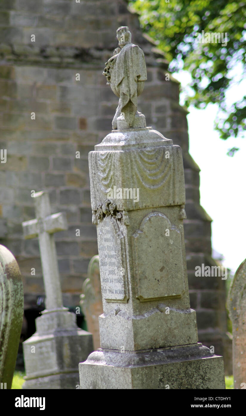 Old gravestone in cemetery with church in background. - Stock Image