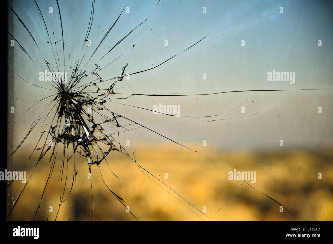 Broken window, cracked glass on urban background - Stock Image