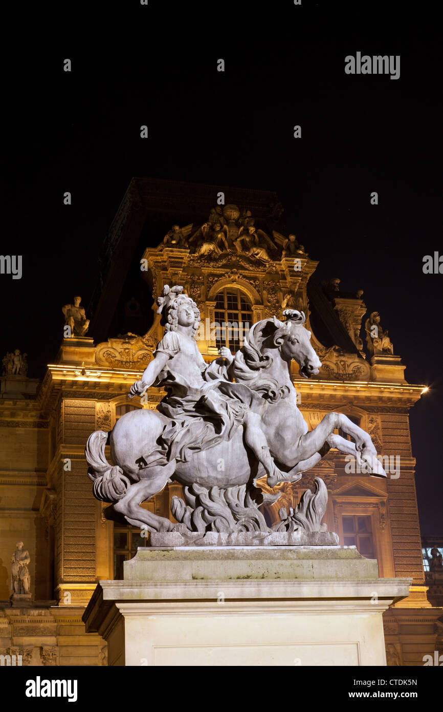 Statue of Louis XIV (Cour Napoleon du Louvre) by Bernini in the Louvre courtyard, illuminated at night. - Stock Image
