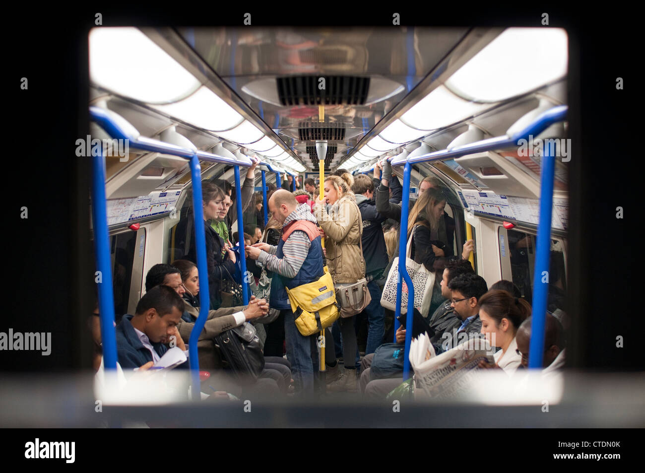 Passengers riding on the London Underground public transport network, also known as the Tube, in London, England. - Stock Image