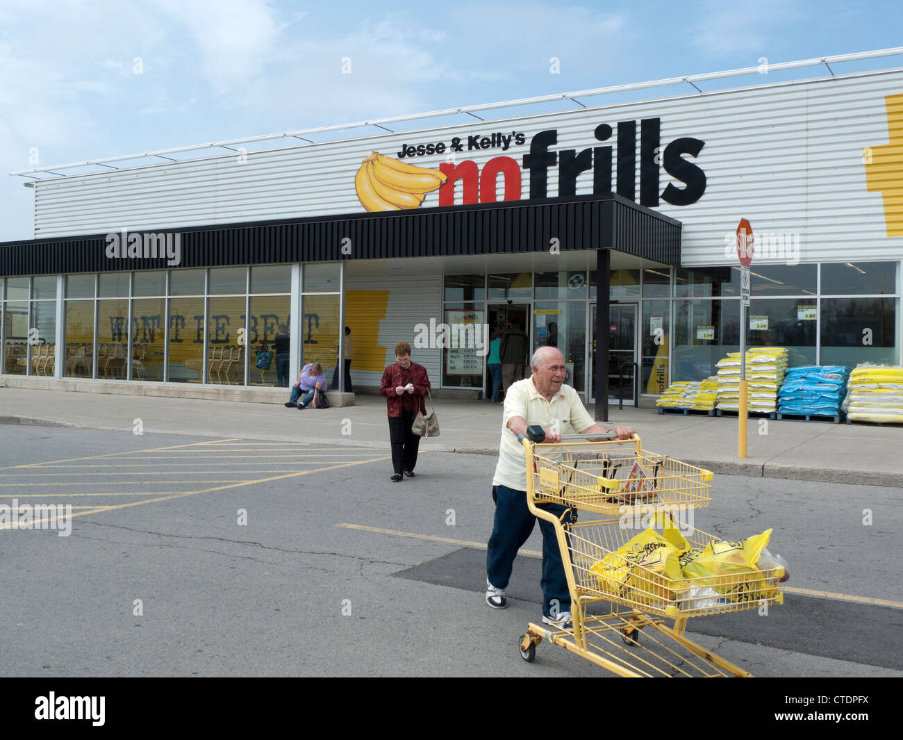 An elderly man pushing a shopping trolley outside Jesse & Kelly's No Frills supermarket store Ontario, Canada, North Stock Photo