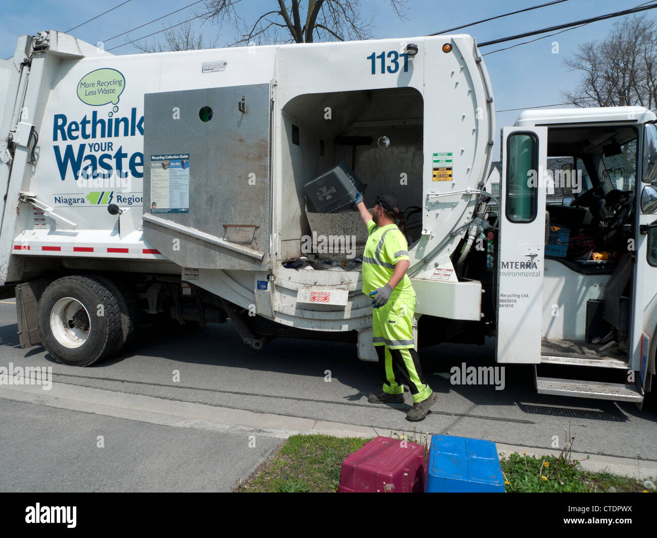 Garbage man loading Rethink Waste truck with household recycled paper Fort Erie Ontario Canada - Stock Image