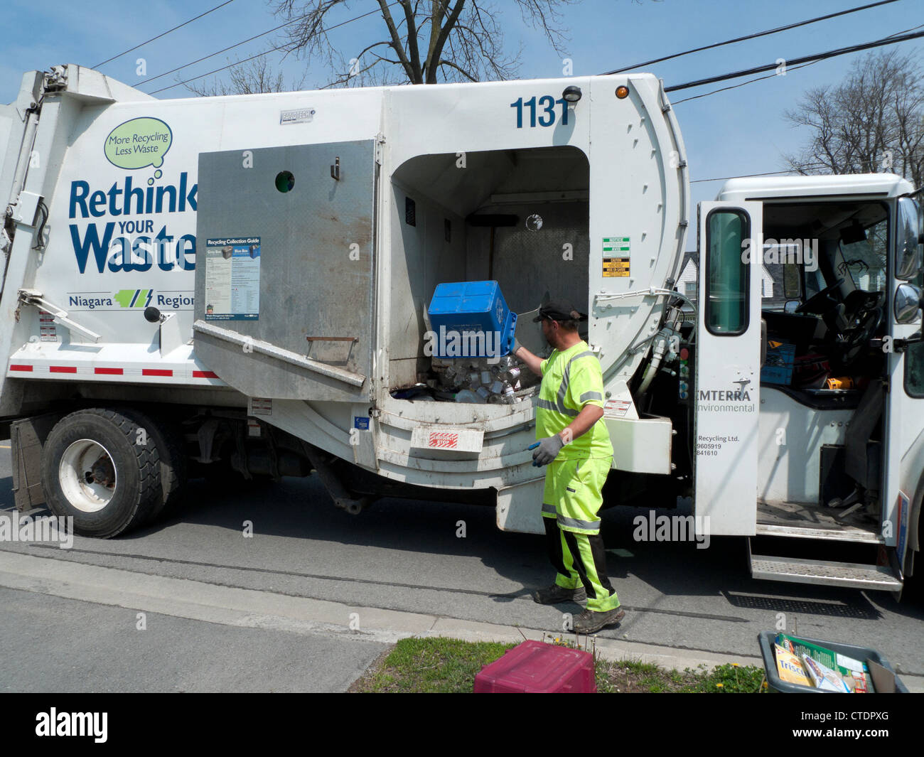 Garbage man loading Rethink Waste truck with household recycled paper Fort Erie Ontario Canada  KATHY DEWITT - Stock Image