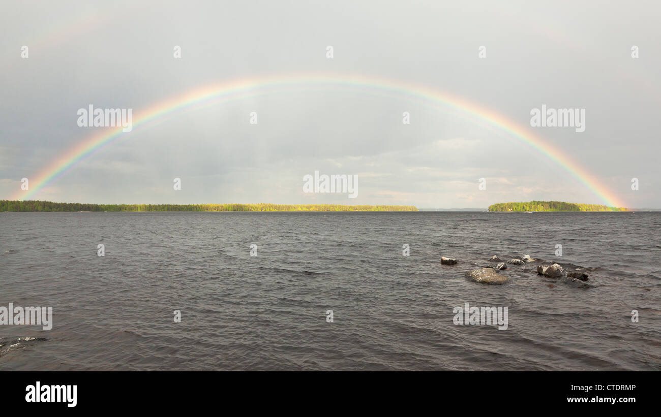Beautiful rainbow on lake in summer. - Stock Image
