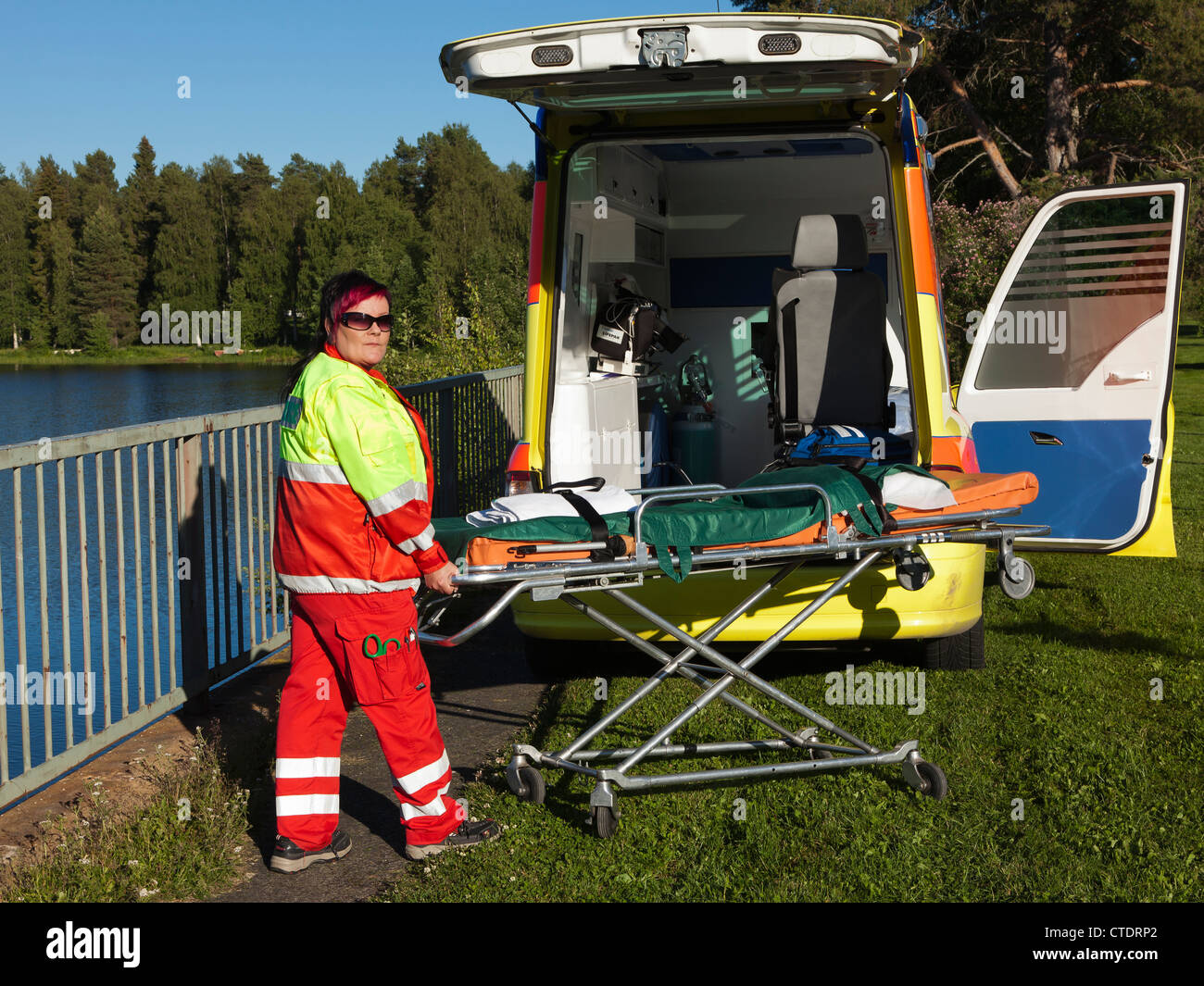 An ambulance and the paramedic by the lake in summer. - Stock Image