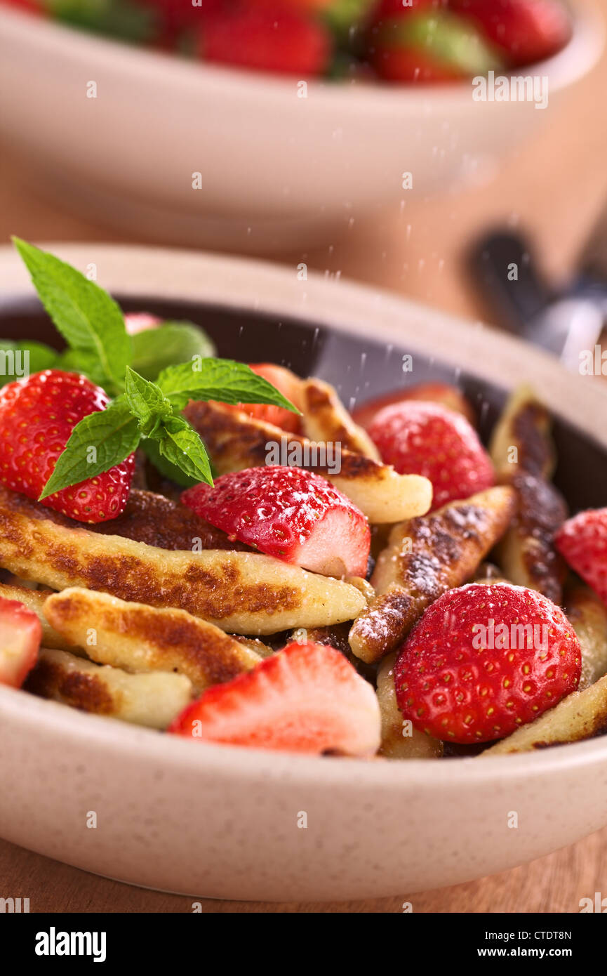 Schupfnudeln (Swabian potato noodles from Southern Germany) with fresh strawberries, cinnamon and sugar powder - Stock Image