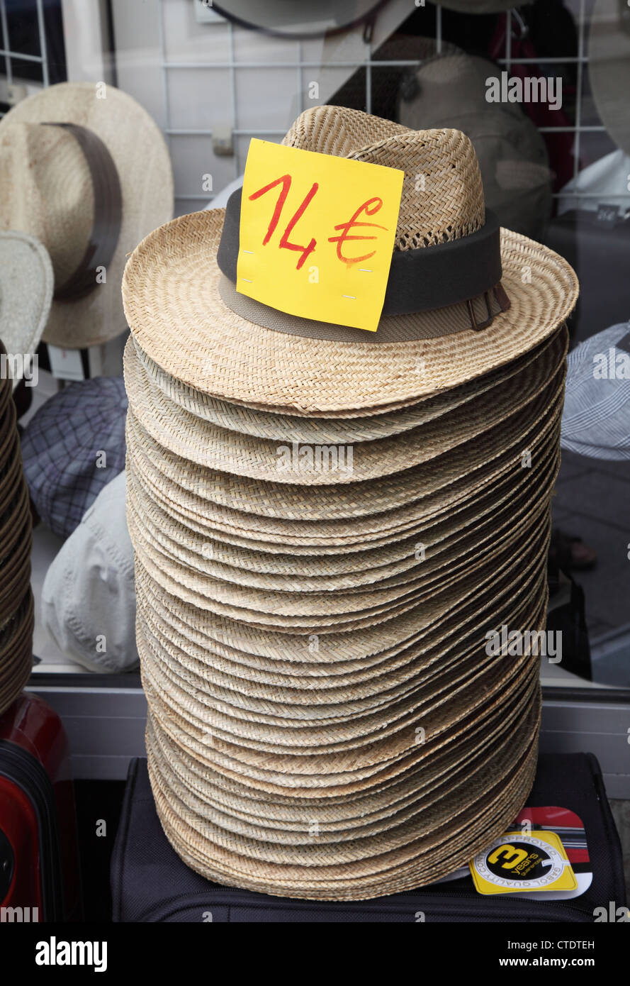 Stack of straw panama hats or boaters within a shop in France - Stock Image