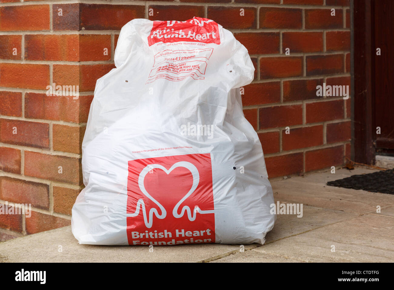5b9492d893 British Heart Foundation charity clothes recycling bag full of old clothing  for collection outside a house. England UK Britain