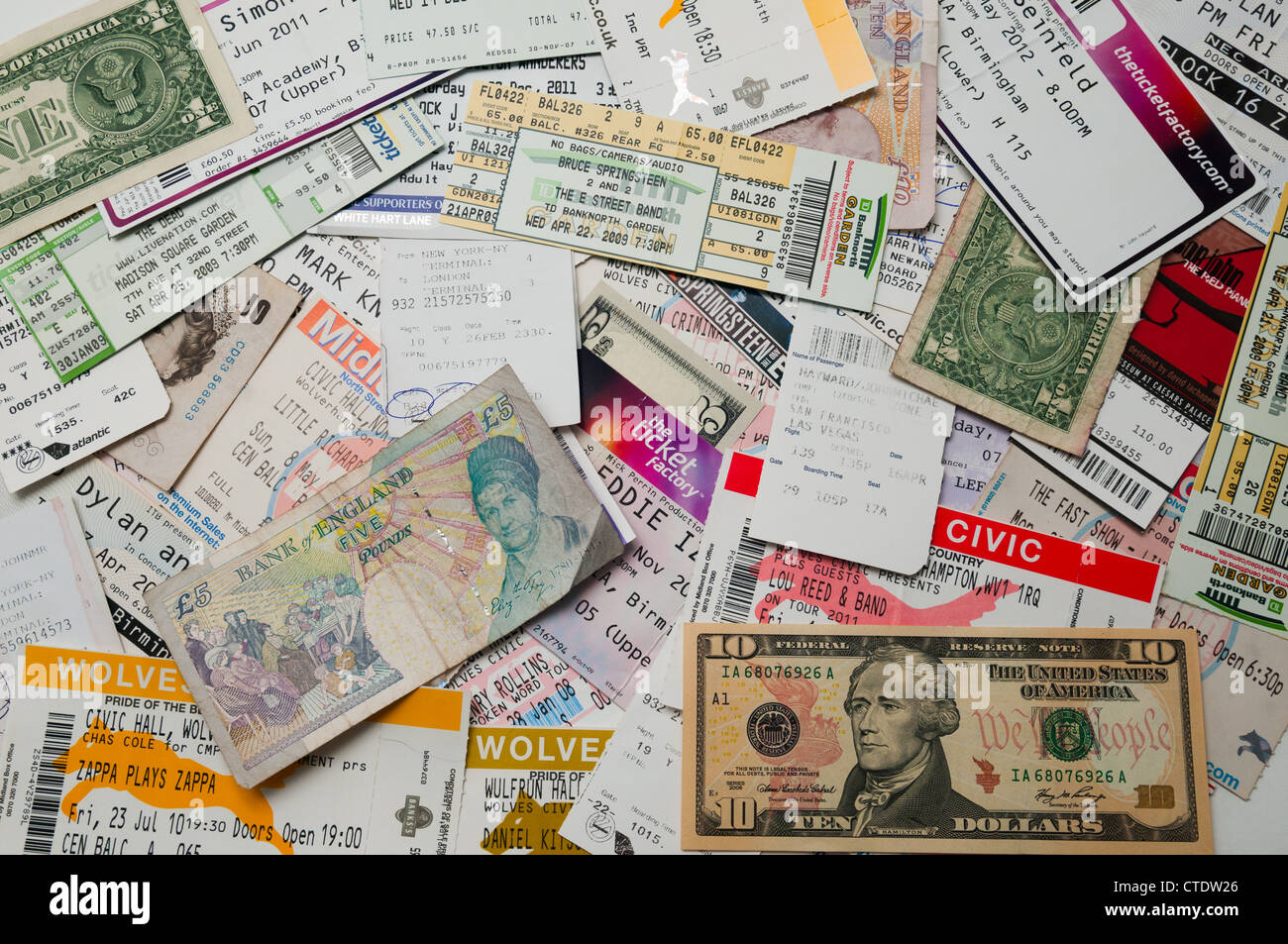 A pile of concert tickets, plane tickets and money - Stock Image