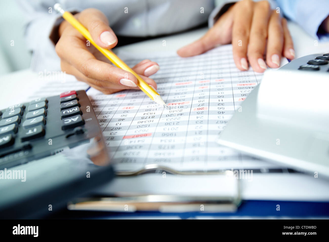 Photo of human hands holding pencil and marking numbers in documents - Stock Image