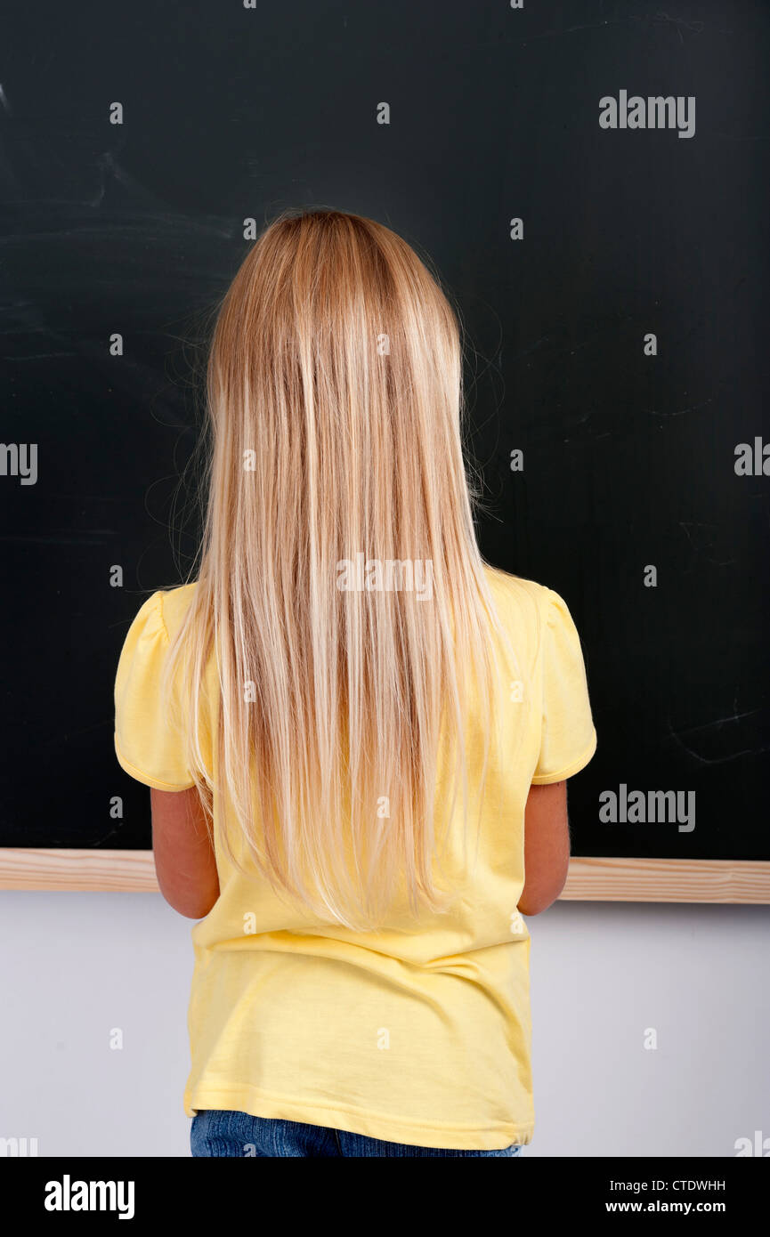back view of a little girl writing on a chalkboard - Stock Image