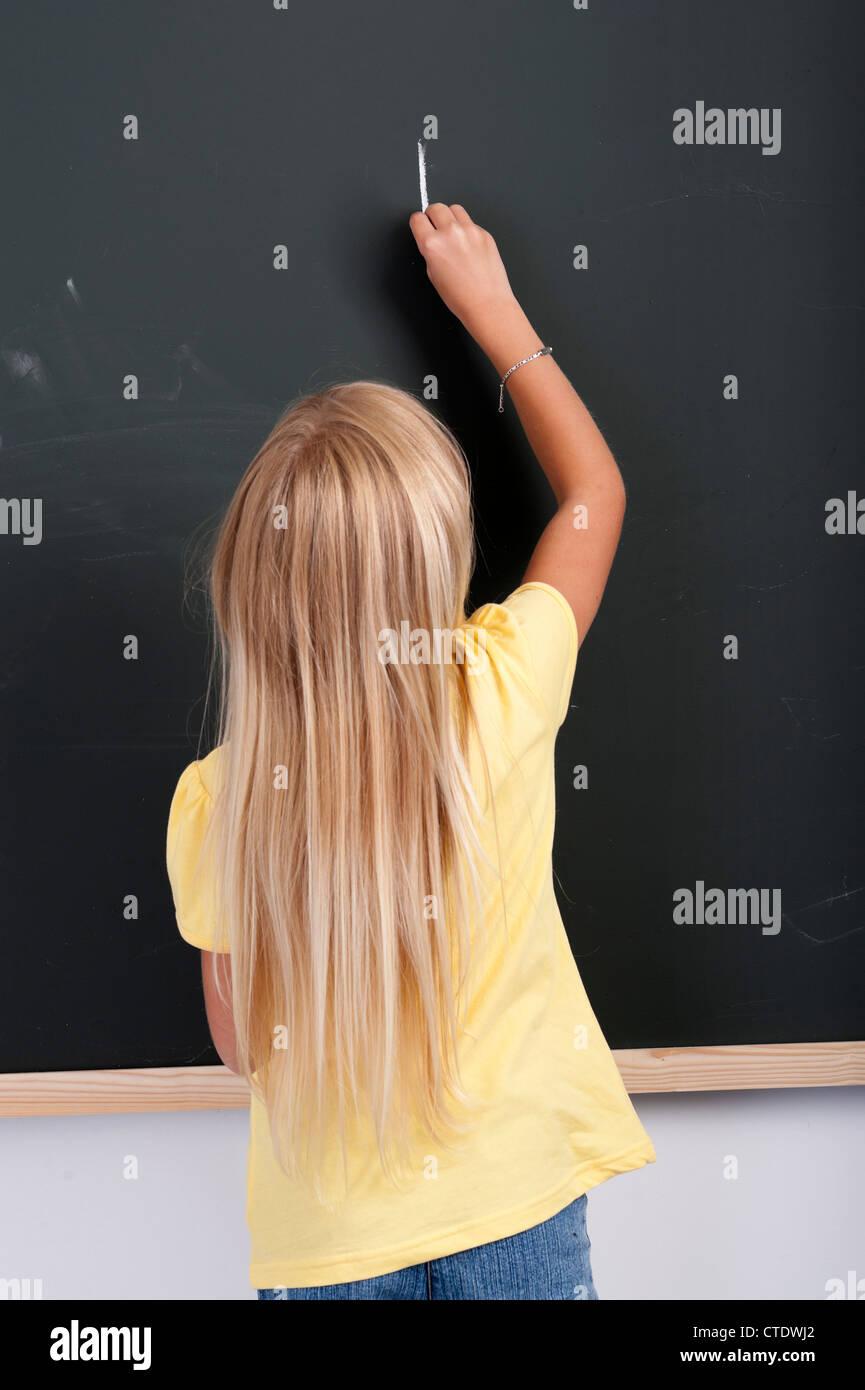 backview of girl writing o a blackboard - Stock Image