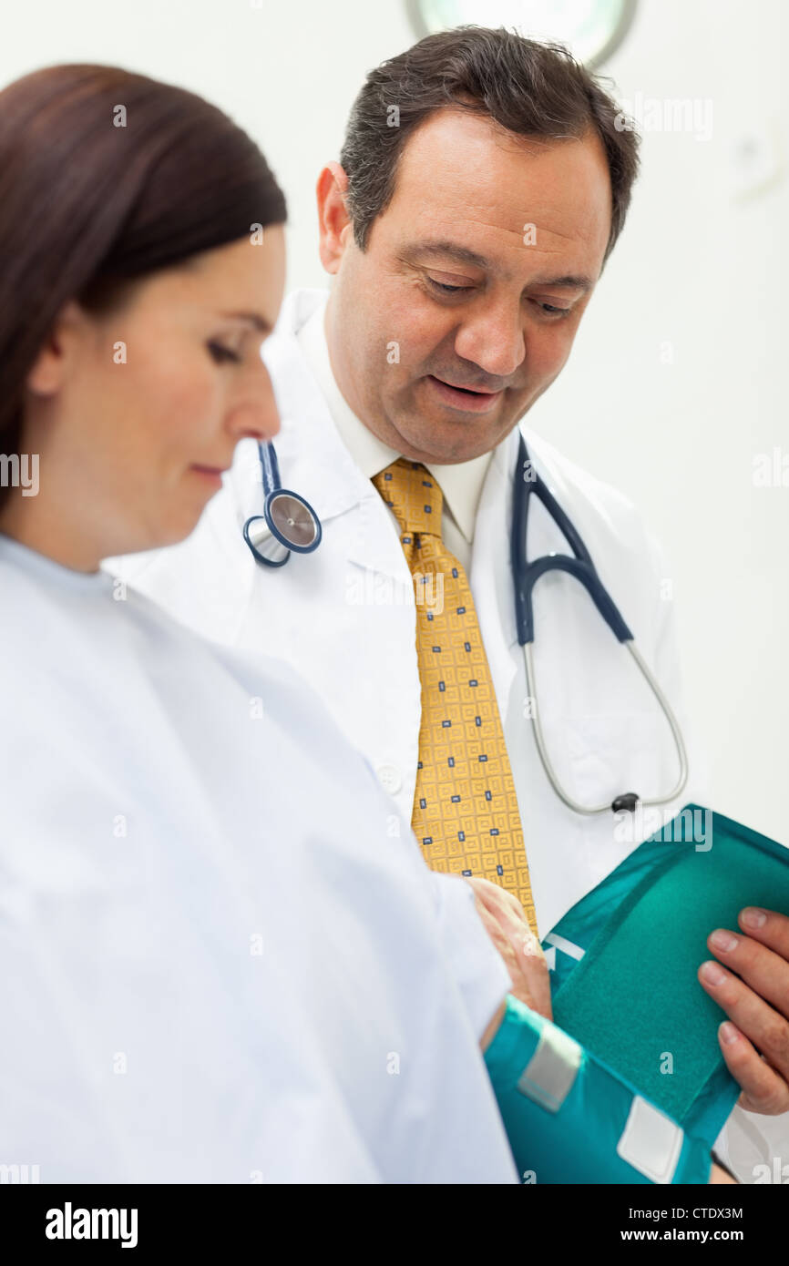 Doctor placing a sphygmomanometer around the arm of his patient - Stock Image