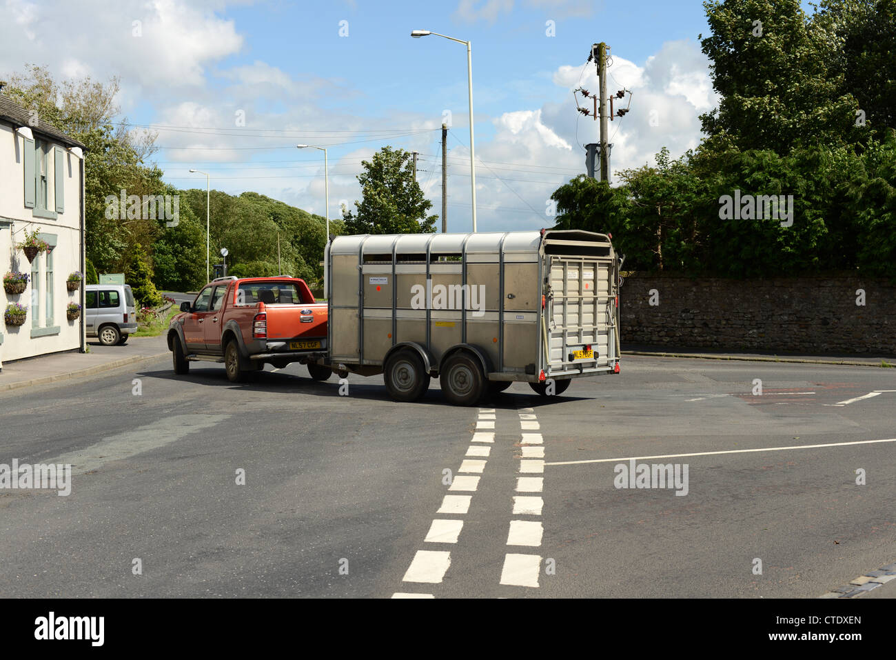 Horse box towed by pick up truck turning right at a junction. UK - Stock Image