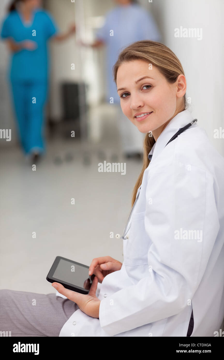 Woman doctor sitting on the floor while holding a tablet - Stock Image