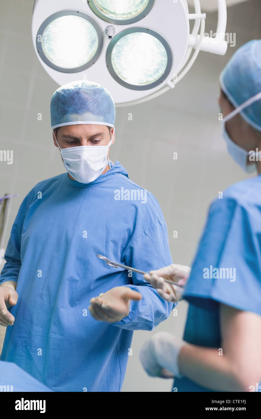Nurse giving surgical scissors to a doctor Stock Photo