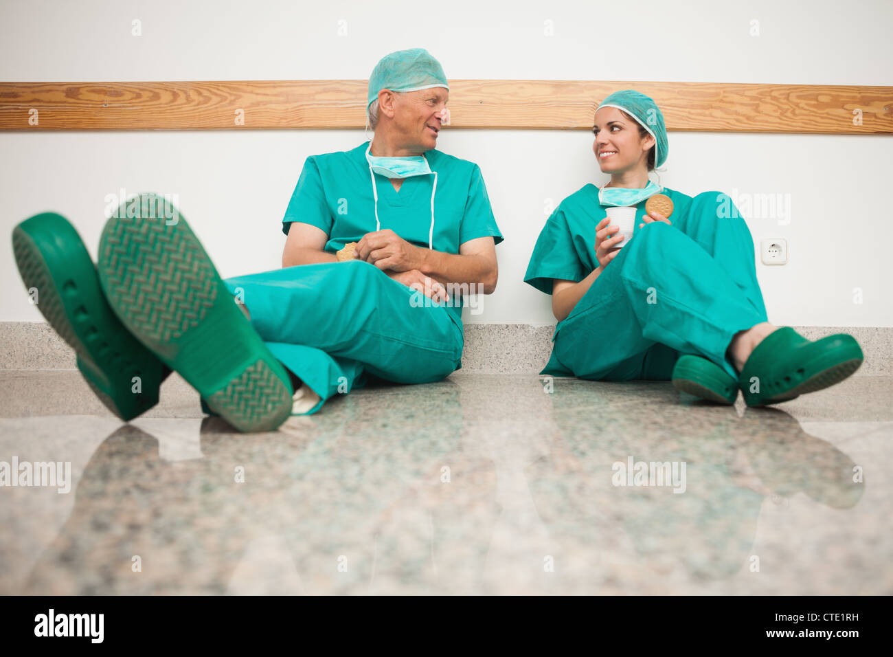 Surgeons talking while sitting in the floor - Stock Image