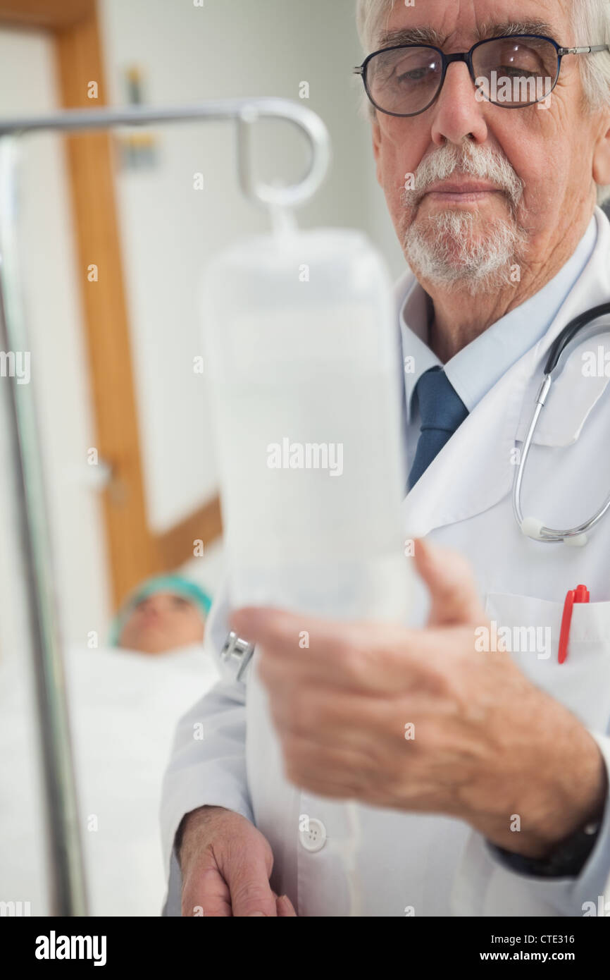 Doctor checking an intravenous drip - Stock Image