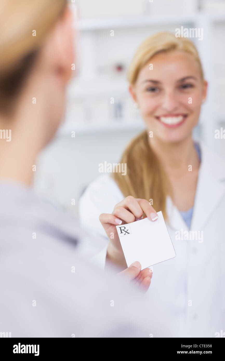 Someone giving a prescription to a pharmacist - Stock Image
