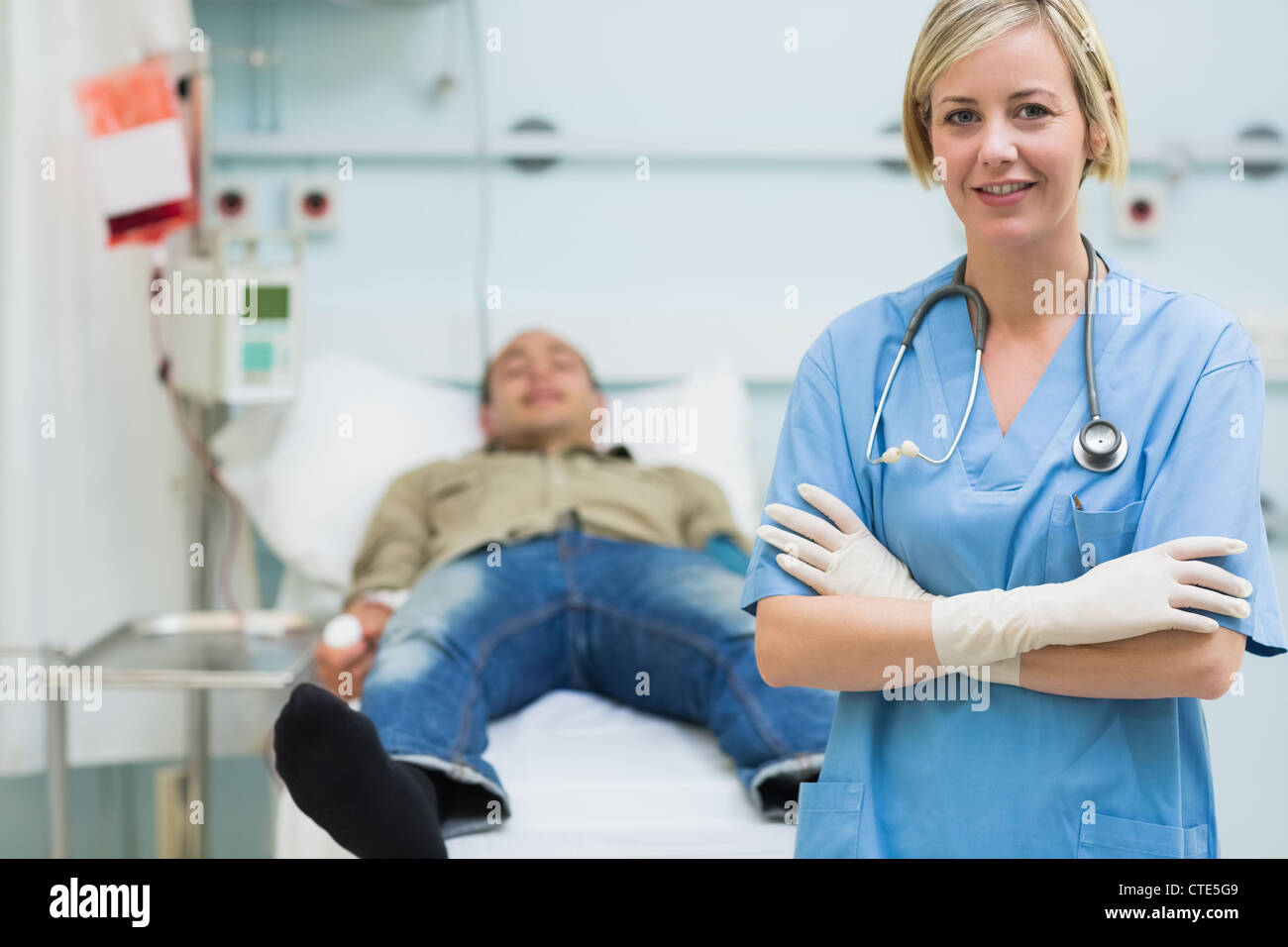 Nurse next to a male patient with arms crossed - Stock Image