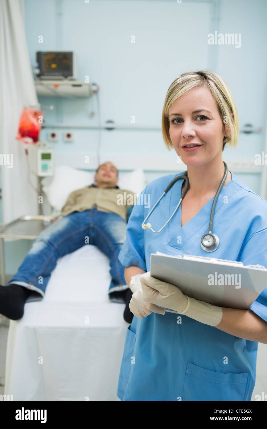 Nurse next to a male patient while holding a clipboard - Stock Image