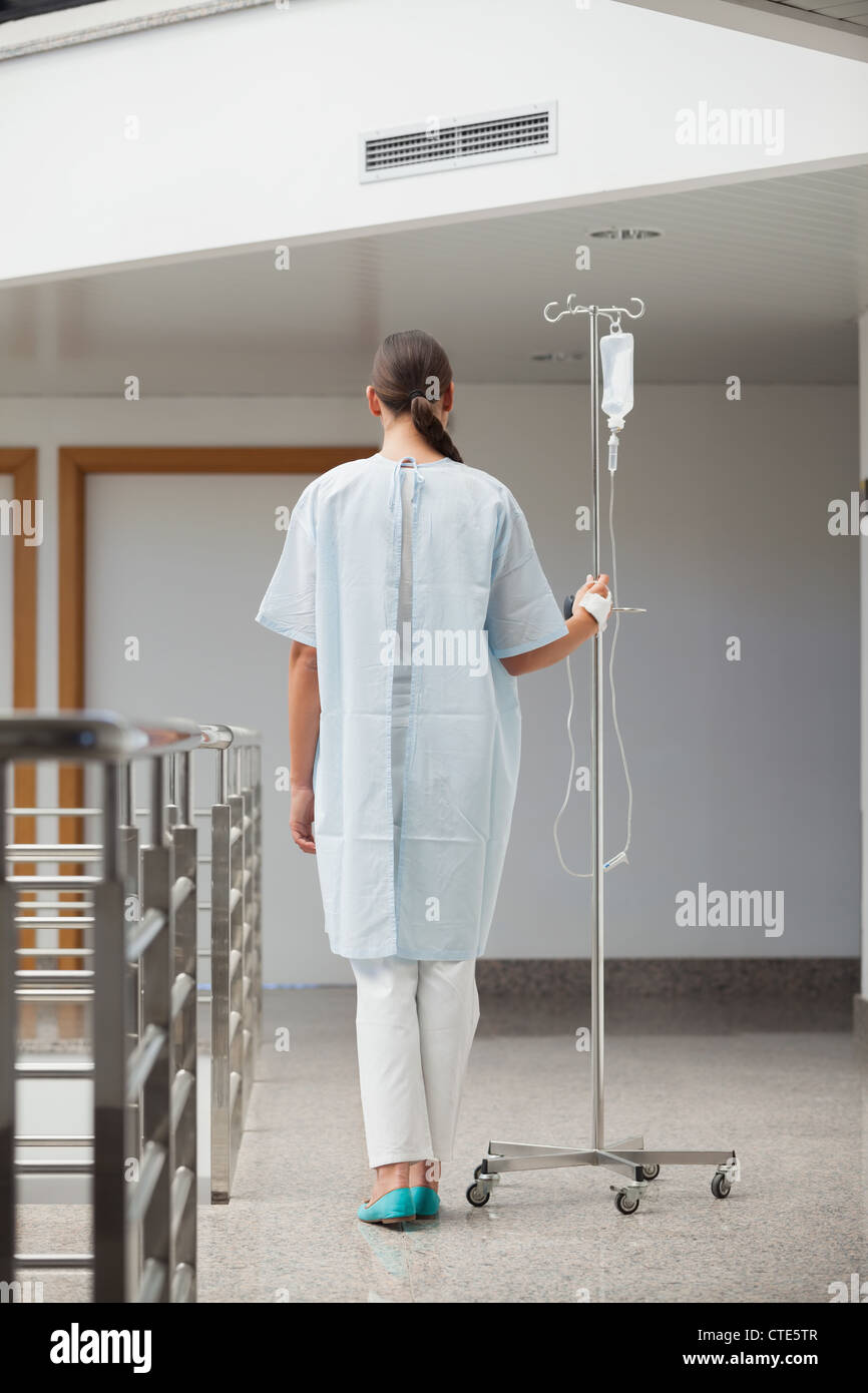Rear view of a patient holding a drip stand - Stock Image