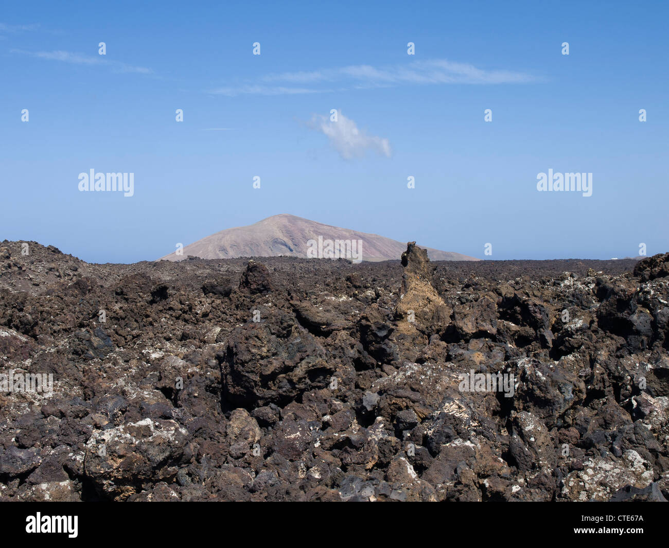 Lava-field with sharp uneven rocks and an old volcano in the background near Timanfaya in Lanzarote - Stock Image