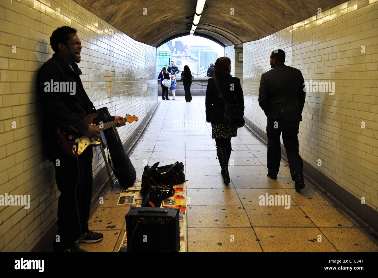 A Busker performs in a London subway - Stock Image