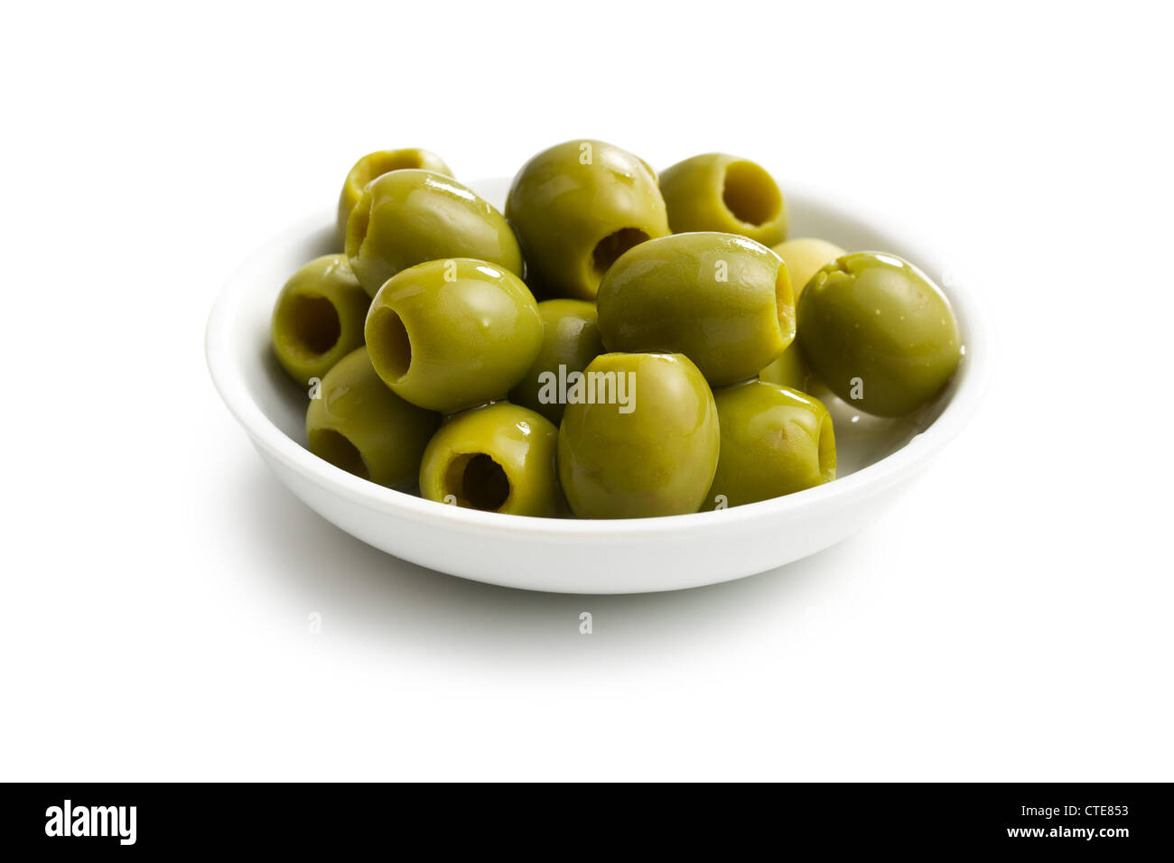 green olives in white bowl on white background - Stock Image
