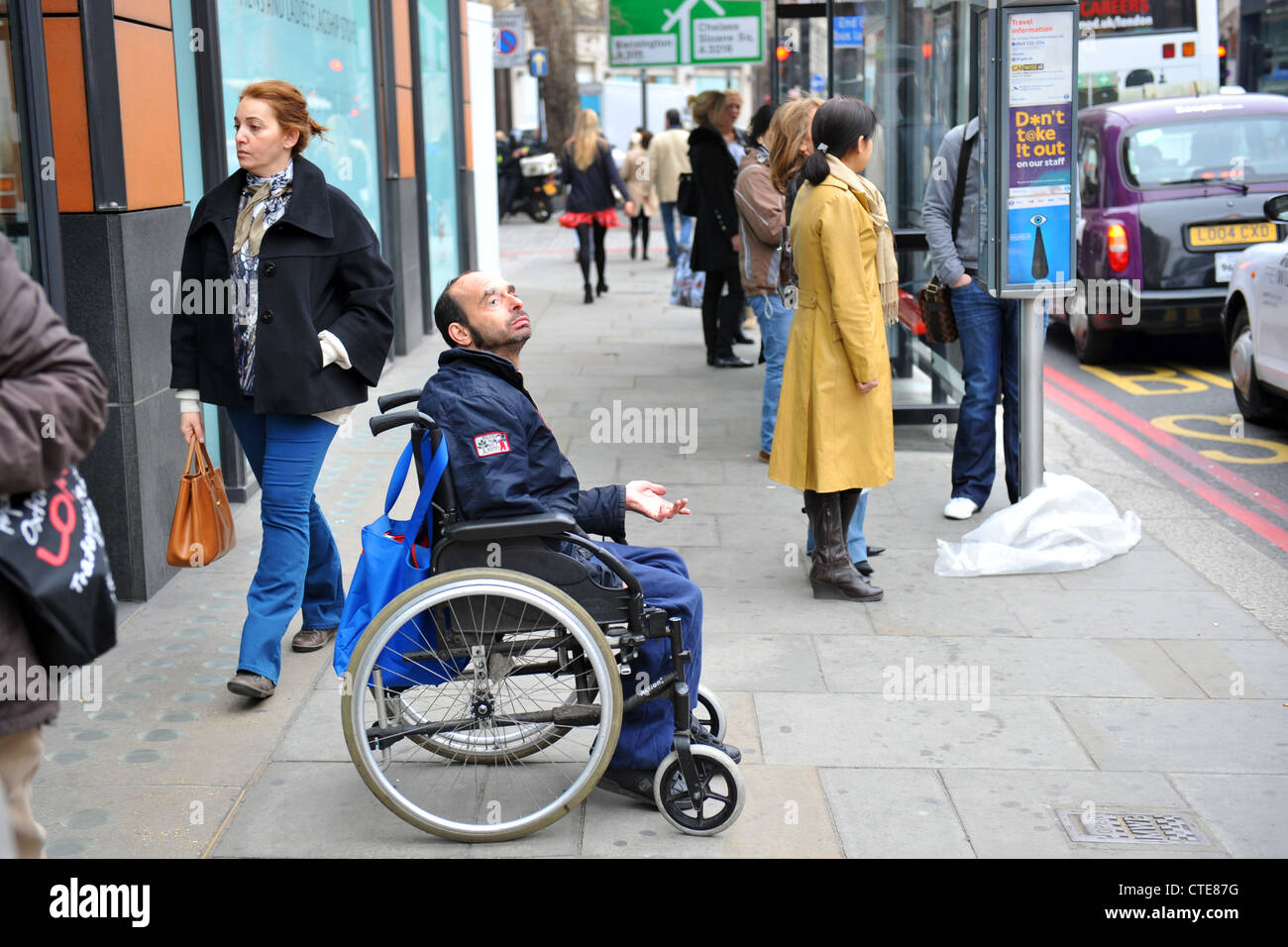A disabled man begs from his wheelchair in Knightsbridge London. - Stock Image