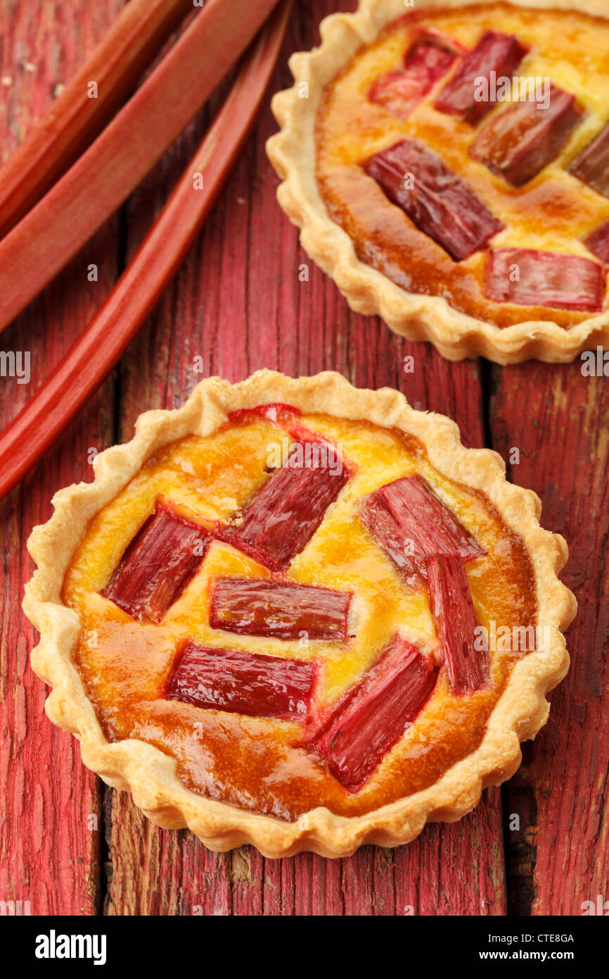 Rhubarb & saffron cream tart on a red wooden background - Stock Image