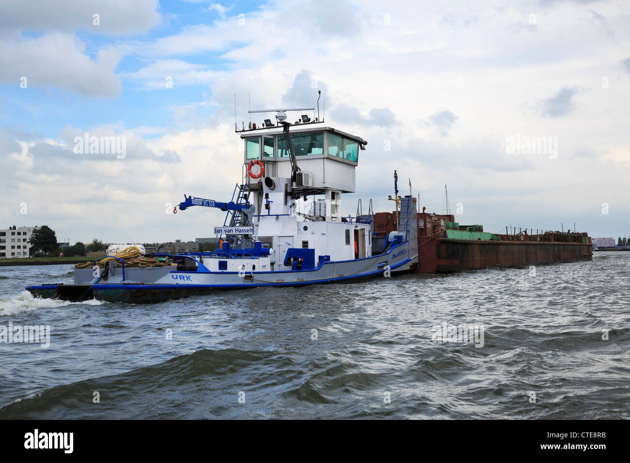 The inland tug Jan Van Hasselt, built in 1953, pushing a barge in the Port of Amsterdam. - Stock Image