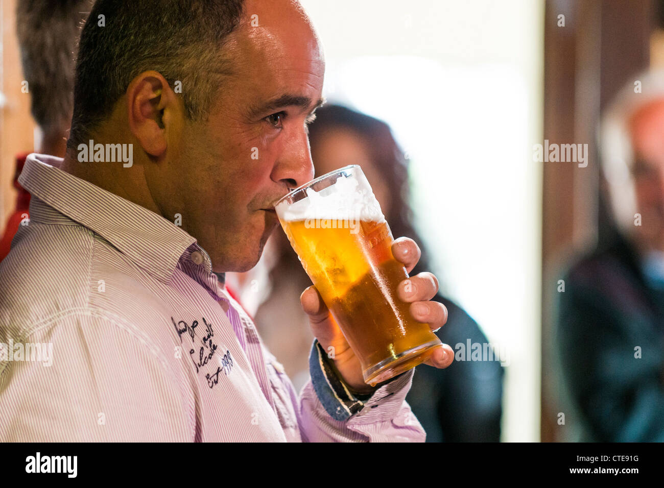 a man drinking a pint of lager beer in a pub uk - Stock Image