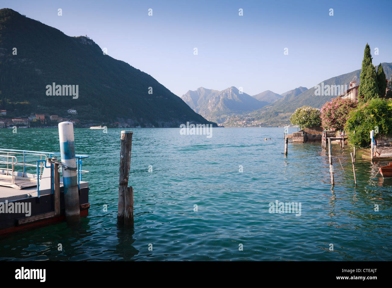 Sulzano, Lago d'Iseo, lake with boat moorings, gardens, island of Monte Isola and mountains behind. - Stock Image