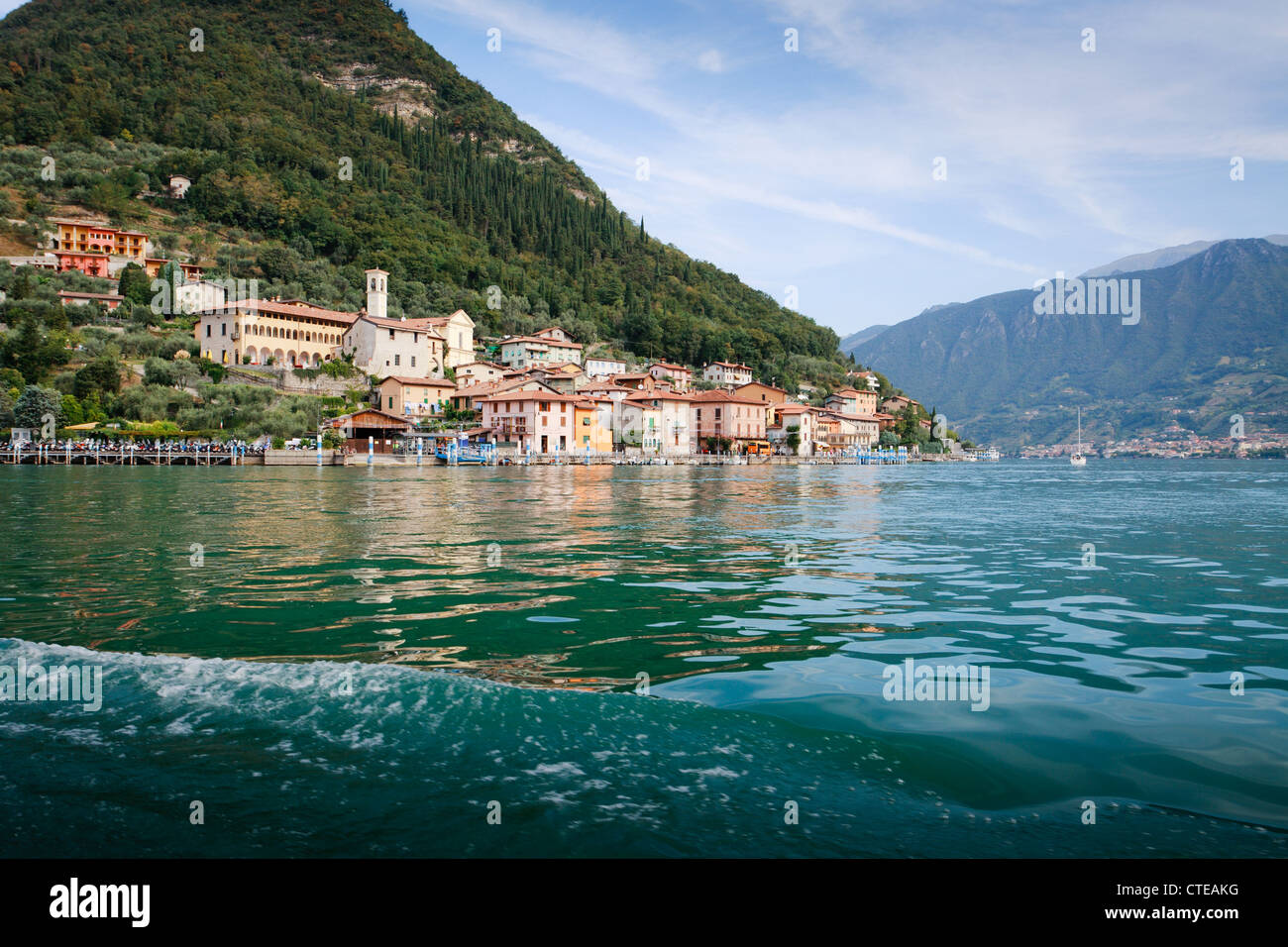 Town of Peschiera, Monte Isola, viewed from boat from Sulzano, with steep hill behind and reflection in water. - Stock Image