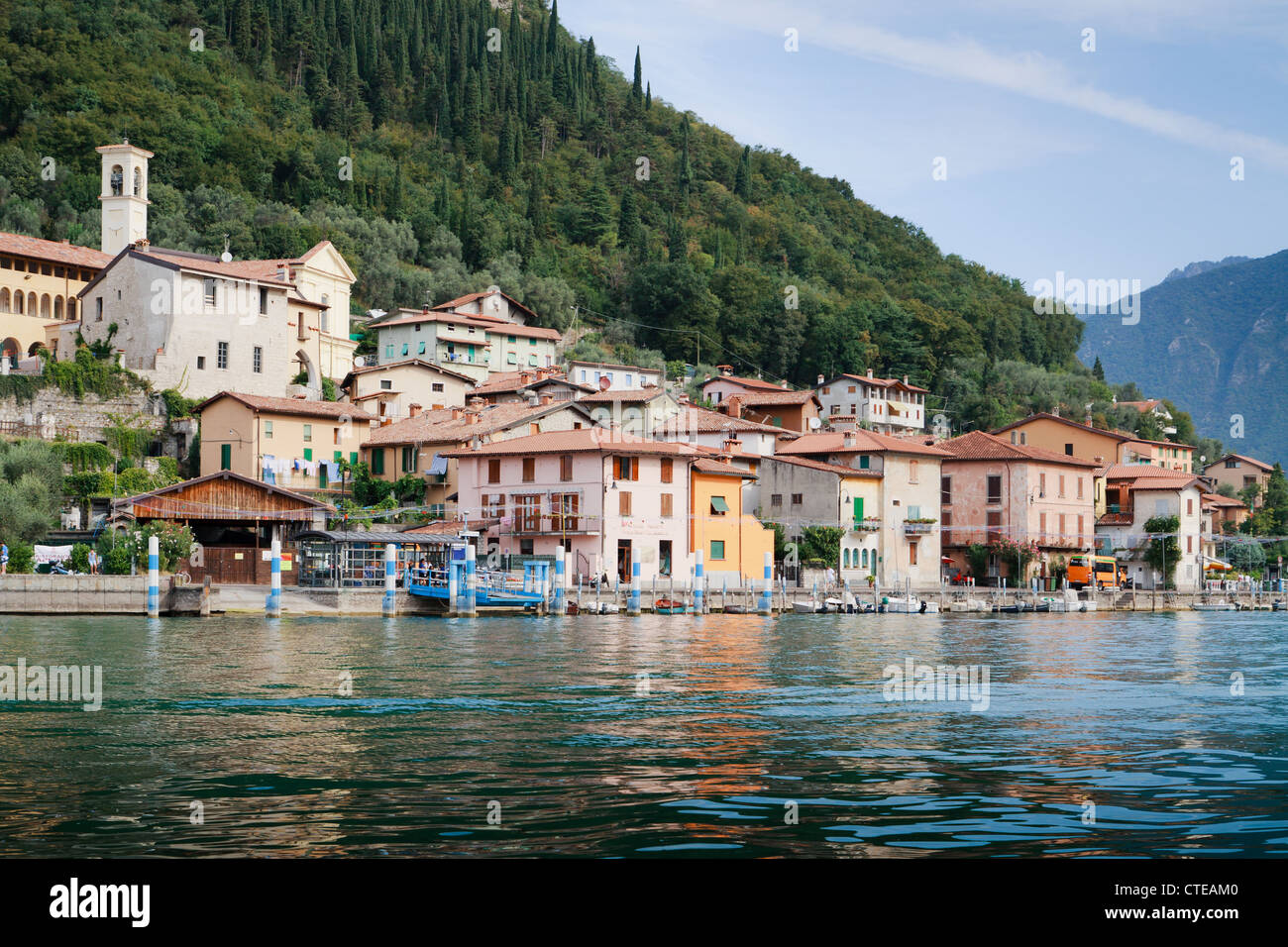 Town of Peschiera from Lago d'Iseo, waterfront with 18th century church on hill behind, on forested island of - Stock Image