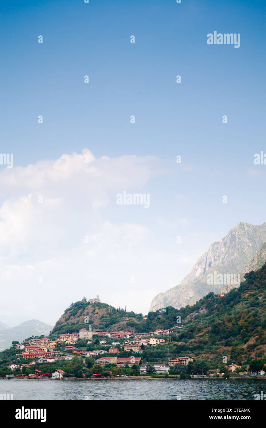 Marone, Lago d'Iseo, church on hilltop, town, lake and mountain in sunlight beyond, with expanse of blue sky. - Stock Image