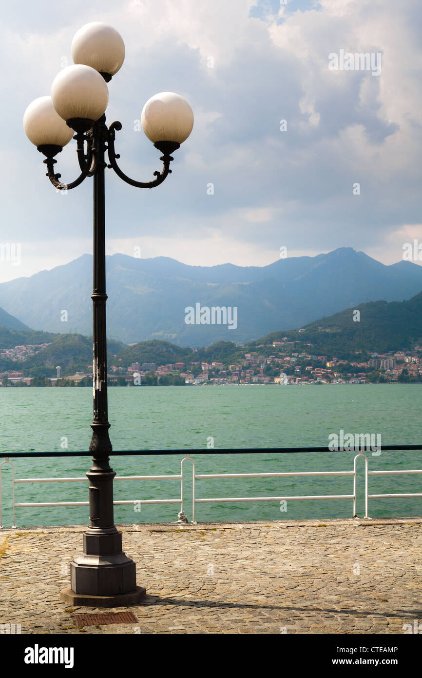 Lamp post and lake-side promenade in Pisogne with distant view of Lovere across Lago d'Iseo, mountains, clouds - Stock Image