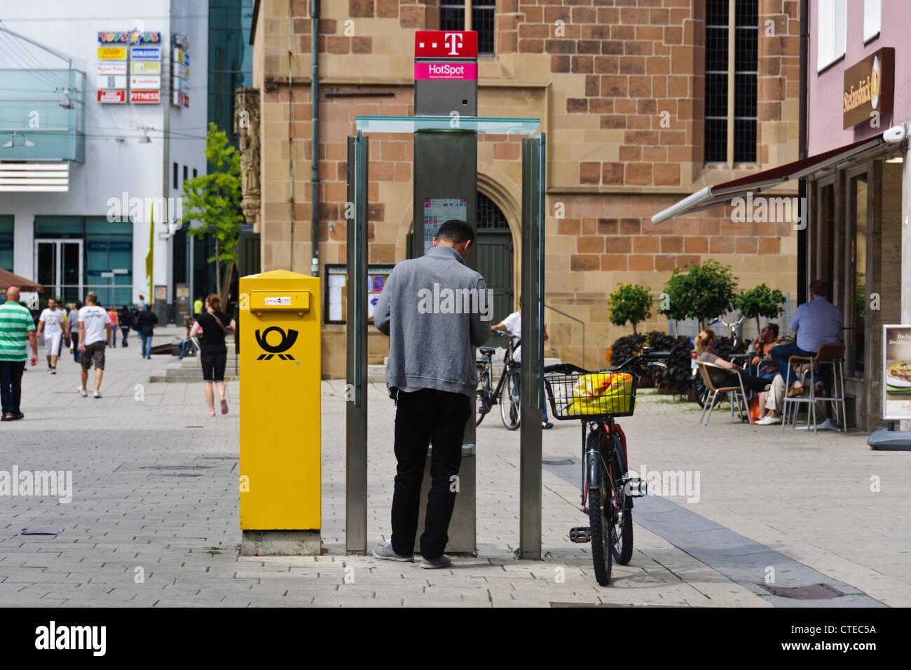 Man in public telephone booth Deutsche Post letterbox