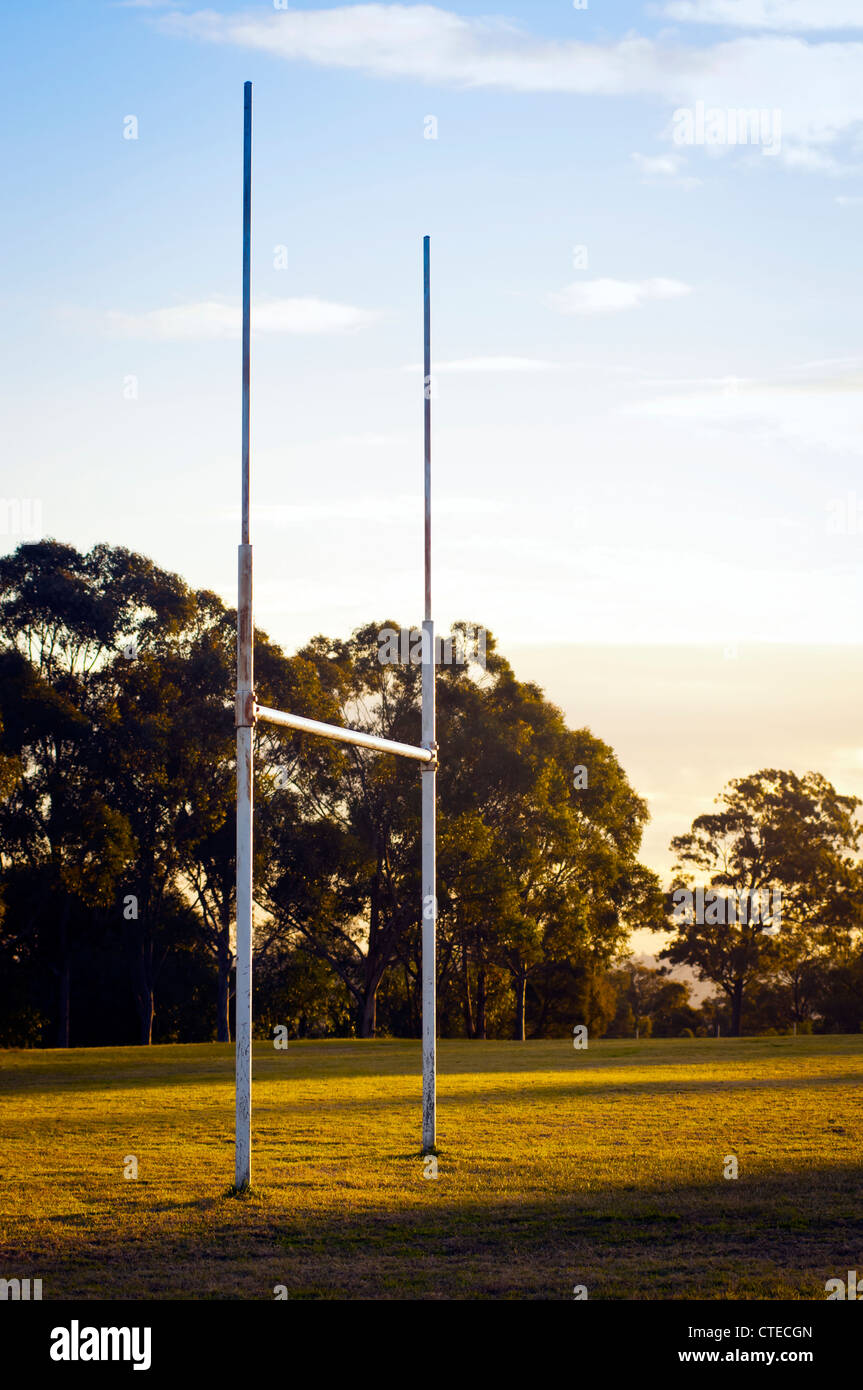 Goal posts for football, rugby union or league on field at sunset - Stock Image