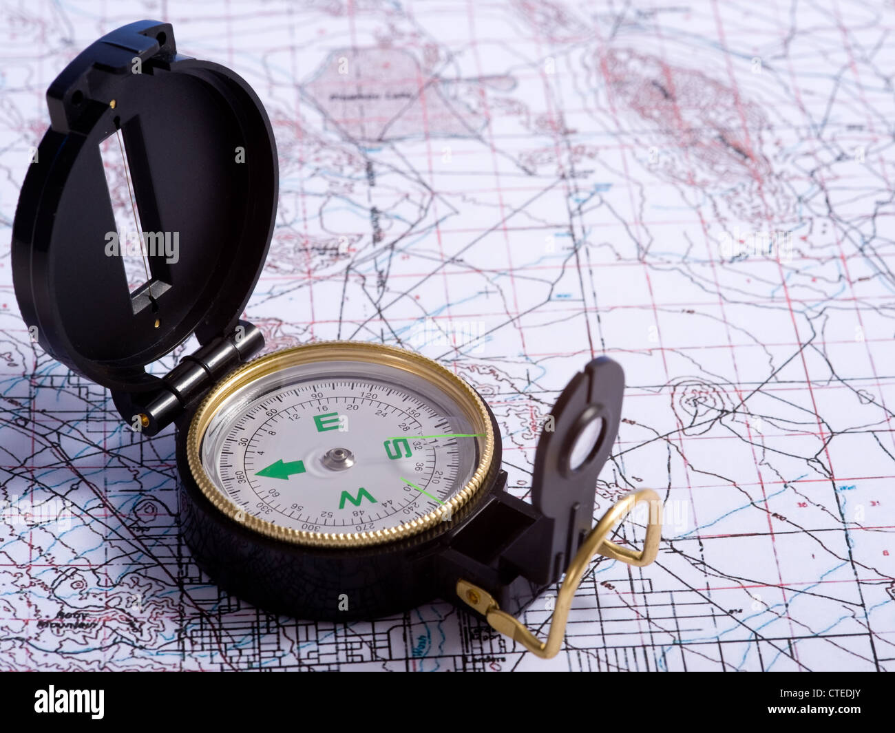A black engineer's compass lying on top of a topographical map - Stock Image