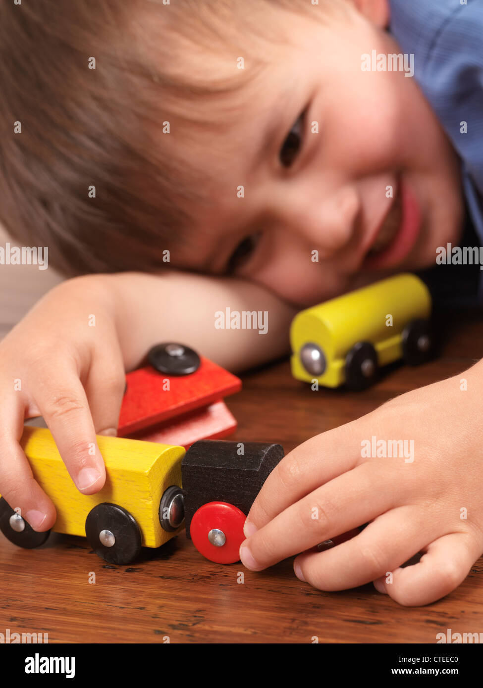 Happy two year old boy playing with a colorful toy train on hardwood floor - Stock Image