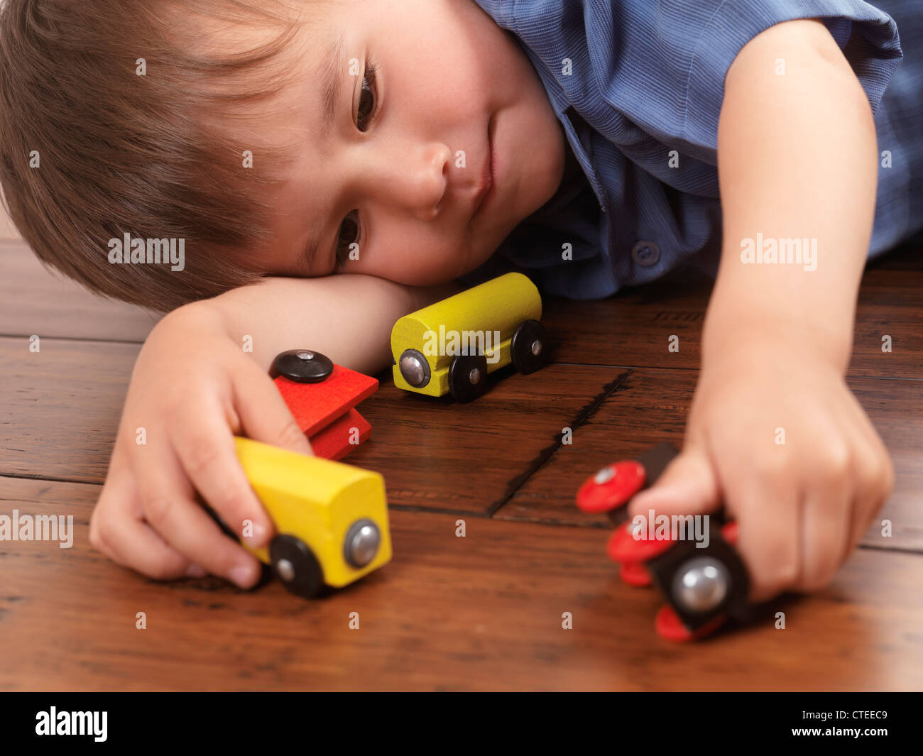 Two year old boy playing with a colorful wooden toy train on hardwood floor - Stock Image